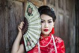 Chinese girl in traditional Chinese cheongsam blessing  Ludzie Obraz