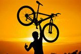 cyclist raising his bike with thumbs up silhouette  Sport Fototapeta