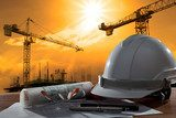 safety helmet and architect pland on wood table with sunset scen  Architektura Obraz