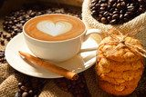 A cup of cafe latte with coffee beans and cookies  Fototapety do Kawiarni Fototapeta
