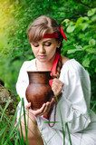 Beautiful young girl with a ceramic jug at the well  Folklor Fototapeta