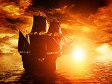 Ancient pirate ship sailing on the ocean at sunset  Pojazdy Fototapeta