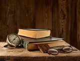 Vintage book, glasses and watches on the background of a wooden  Sepia Fototapeta