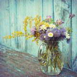 bouquet of garden flowers and healing herbs in glass jug on old  Salon Plakat