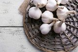 Fresh garlic on wicker mat, on wooden background  Obrazy do Kuchni  Obraz