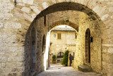 Street with arches in an old town from Tuscany  Uliczki Fototapeta