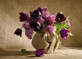 Beautiful bouquet of tulips with sprigs of lilac in a vase on a  Kwiaty Obraz