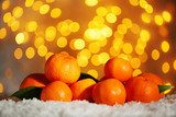 Fresh ripe mandarins on snow, on lights background  Owoce Obraz