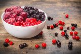 frozen berries in plate on wooden background  Obrazy do Kuchni  Obraz