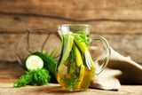 Glass ewer with fresh organic cucumber water on wooden table  Obrazy do Kuchni  Obraz