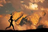 Silhouette of a woman running jogging in the mountains at sunset  Fototapety do Klubu Fitness Fototapeta