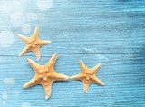 Three starfish on a blue wooden background Styl Marynistyczny Fototapeta