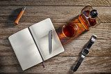 Overhead view of a notebook, whiskey, a knife, and a watch Plakaty do Biura Plakat