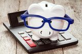 Piggy bank in glasses with calculator Plakaty do Biura Plakat