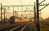 Freight train moving on the tracks at sunset Industrialne Fototapeta