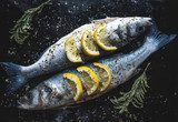 Sea bass fish with lemon on blackboard. Preparing for grill Obrazy do Jadalni Obraz