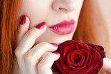 Portrait with red rose flower. Dark red lips and nails. Beautiful red-haired young woman. Obrazy do Salonu Kosmetycznego Obraz