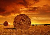 Straw bales on farmland with red cloudy sky  Zachód Słońca Fototapeta