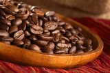 Roasted coffee beans on wooden plate on red cloth  Kawa Fototapeta