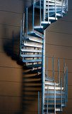 Metal spiral staircase casting shadow on wall in evening light  Schody Fototapeta