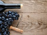 Bottle of wine, corkscrew and grape on wooden background  Obrazy do Kuchni  Obraz