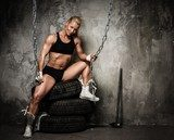 Beautiful muscular bodybuilder woman sitting on tyres  Fototapety do Siłowni Fototapeta