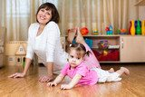 Mother and her child doing exercises together in home interior  Fototapety do Klubu Fitness Fototapeta
