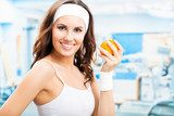 Woman with orange, at fitness center  Fototapety do Klubu Fitness Fototapeta