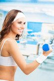 Woman exercising with dumbbell, at fitness center  Fototapety do Klubu Fitness Fototapeta