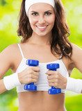 Woman exercising with dumbbell, outdoors  Fototapety do Klubu Fitness Fototapeta