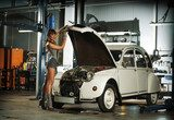 A beautiful brunette woman in a garage fixing an old car  Pin-up Obraz