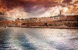 view of the city and sea port on the background of dramatic suns  Prowansja Fototapeta