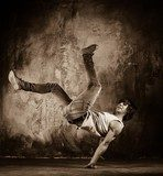 Young man with naked torso doing acrobatic movements  Sepia Fototapeta