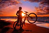 Woman with bicycle on the beach  Sport Fototapeta