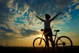 Biker-girl at the sunset on the meadow  Sport Fototapeta