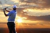 Man playing golf against sunset  Sport Fototapeta
