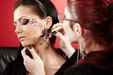 Brunette having applied face tattoo by makeup artist  Obrazy do Salonu Kosmetycznego Obraz