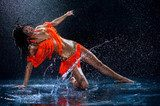 Woman dancing under rain in orange dress. Studio  Fototapety do Szkoły Tańca Fototapeta