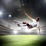 football player striking the ball  Stadion Fototapeta