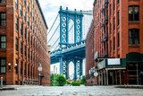 Manhattan Bridge between Manhattan and Brooklyn over East River seen from a narrow alley enclosed by two brick buildings on a sunny day in Washington street in Dumbo, Brooklyn, NYC Mosty Obraz