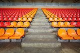 Rows of red and orange plastic sits at stadium  Stadion Fototapeta