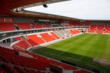 View on an empty football (soccer) stadium with red seats  Stadion Fototapeta