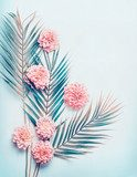 Creative layout with tropical palm leaves and pastel pink flowers on  turquoise blue desktop background, top view, place for text, vertical Kwiaty Obraz