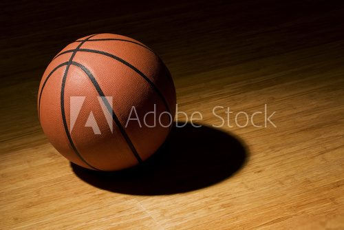 Basket ball sitting on wood floor  Stadion Fototapeta