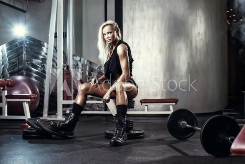 fitness blonde sexy girl on bench in the gym in military style  Fototapety do Klubu Fitness Fototapeta