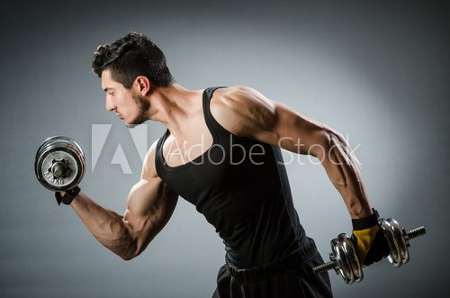Muscular ripped bodybuilder with dumbbells  Fototapety do Klubu Fitness Fototapeta