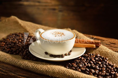 A cup of cappuccino and coffee beans on old wooden background  Fototapety do Kawiarni Fototapeta