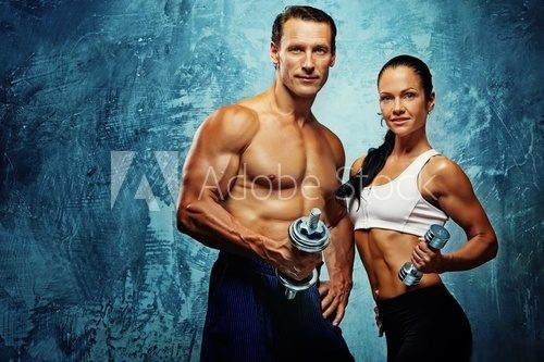 Athletic man and woman with a dumbells.  Fototapety do Siłowni Fototapeta