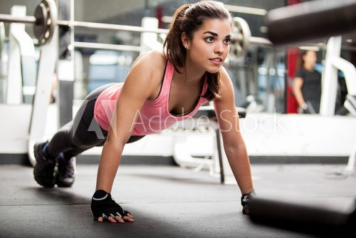 Cute brunette working out at a gym  Fototapety do Klubu Fitness Fototapeta